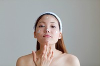 Young Woman Applying Moisturiser