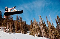 Extreme snowboarder flies off of a jump at the Taos Ski Valley terrain park in New Mexico.