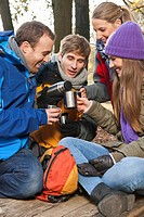 Germany, Berlin, Wandlitz, Friends drinking hot beverage, smiling