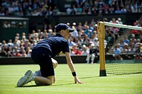 England, London, Wimbledon. A ball boy in a crouched position by the net on Centre Court at The Wimbledon Tennis Championships 2011.