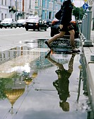Pedestrian crossing a puddle in Wolchonka Uliza street, Moscow, Russia, Europe