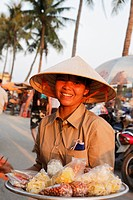 Woman offering sweets in harbor, Hoi An, Annam, Vietnam