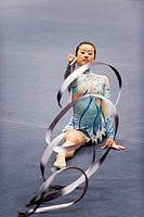 Female gymnast performing floor routine with ribbon