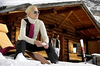Blond woman in front of alpine hut, Alto Adige, South Tyrol, Italy, Europe