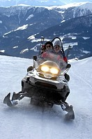 Three people on a snowmobile in the mountains, Alto Adige, South Tyrol, Italy, Europe