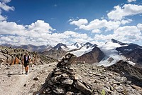 Hiker ascending Finailspitz Mountain in the Schnalstal Valley via the Tisental Valley, with Similaun Mountain and Hintere Schwaerze Mountain at the re...