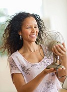 Hispanic woman holding old_fashioned fan