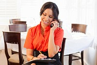 Mixed race woman talking on telephone in restaurant