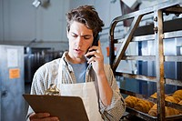 Caucasian baker talking on telephone in bakery