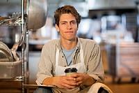 Caucasian baker drinking coffee in bakery