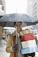 Man carrying Christmas gifts in city