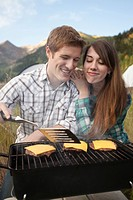 Caucasian couple cooking hamburgers on grill