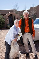 Caucasian couple standing with dog in driveway