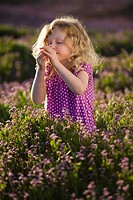 Caucasian girl smelling flowers