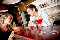 Hispanic woman drinking cocktail talking to bartender
