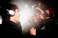 DJ playing music for crowd in nightclub