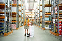 Worker standing with hand truck in warehouse