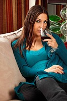 Beautiful woman drinking wine at home