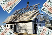 Euro banknotes in front of a house under construction, symbolic image for construction costs