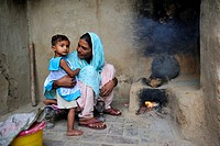 Woman holding her daughter in her arms while cooking with a simple clay oven, she lives and works with her family under the slavery-like practice of d...