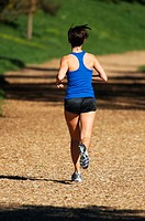 The back of a woman as she runs away on a wood-chip running path