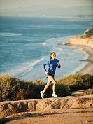 USA, California, San Diego, Woman jogging along sea coast