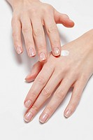 Close up of woman´s hands applying moisturizer, studio shot