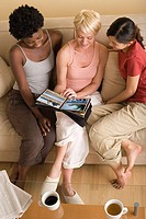 Three girlfriends looking at photo album