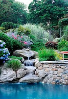 POOLSIDE WITH COLOURFUL GARDEN AND WATERFALL