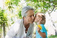 Little girl kissing grandmother on cheek