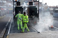 road construction workers installing hot applied high friction road surfacing Belfast Northern Ireland UK
