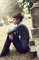 A Young Woman Sits Alone On The Ground Beside A Tombstone, Edmonton Alberta Canada