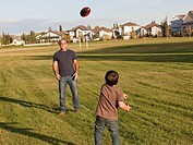 father and son playing football in a park, beaumont alberta canada