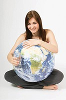 Woman holding a globe and a plastic water bottle