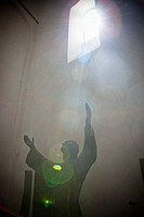 Sunlight Shining Through A Window Onto A Statue With Arms Raised, San Frutuozzo Liguria Italy