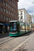 tramway traveling by buildings, helsinki, finland