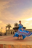a woman dancing in a traditional folkloric dress in the early morning downtown, todos santos baja california sur mexico