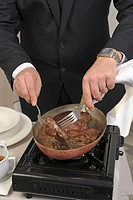 Preparing steak with black pepper sauce on a carving table