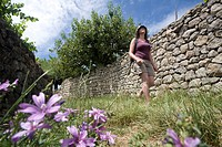France, Ardeche, Payzac, a hiker past a traditional stone wall