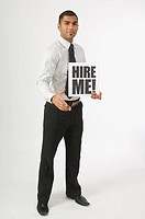 Man holding a hire me sign