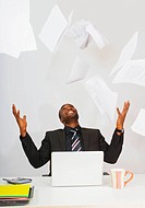 Businessman throwing paperwork in the air