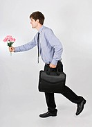 Young businessman walking with briefcase and flowers