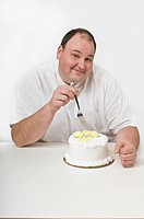 Overweight man about to eat a cake