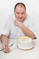 Overweight man looking at cake