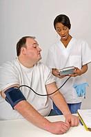 Nurse checking overweight man´s blood pressure