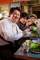 South Korea, Seoul, Dongdaemun District, young men drinking Korean alcohol soju at the table of a restaurant in the covered market