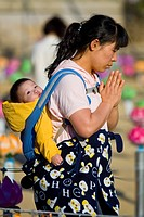 South Korea, South Gyeongsang Province, Haein Buddhist Temple, woman carrying her baby on the back in a typically Korean style and praying in the temp...
