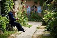 France, Cote d´Or, Chateauneuf en Auxois, labeled Les Plus Beaux Villages de France The Most Beautiful Villages of France, old man fingering currants