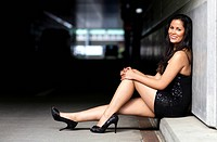 Young woman with long dark hair, short dress and high heels posing sitting