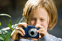 Girl, eight years, taking pictures with a digital camera